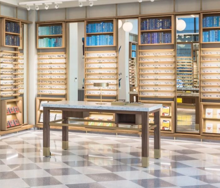 warby parker table in front of shelves holding glasses